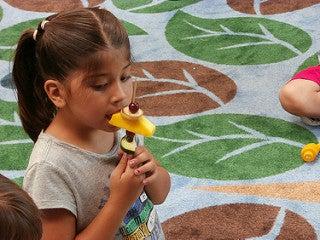Bambina che mangia frutta obesità infantile