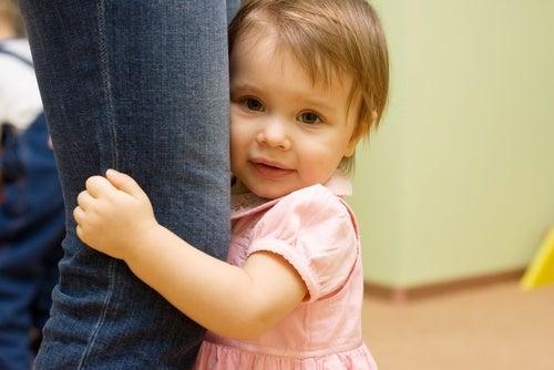Bambina si aggrappa alla gamba della mamma per mancanza di stimoli