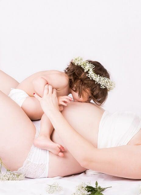 incinta-con-bambina-baciando-la-pancia