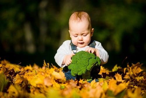 neonato con broccoli tra le mani