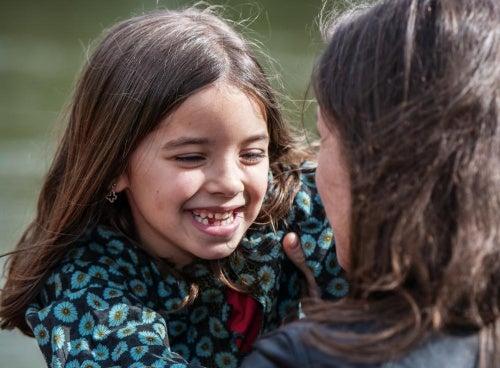 Bambina che sorride con la madre comunicazione con i nostri figli