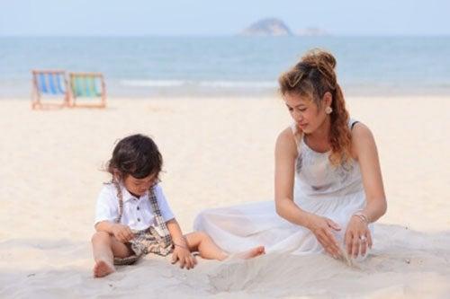 mamma single gioca-con-bambino-in-spiaggia
