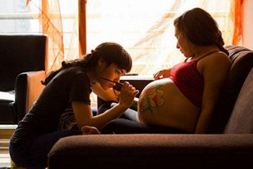 ragazza-disegna-pancia-di-donna-incinta