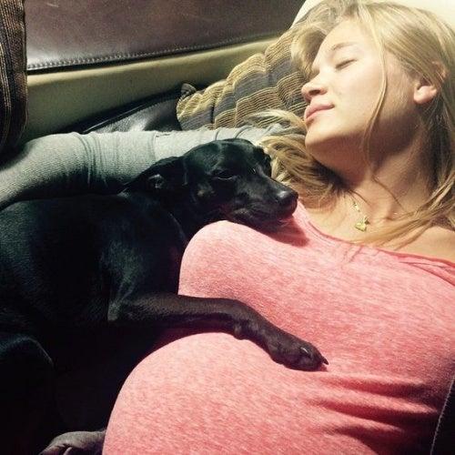 Donna incinta dorme con il suo cane.