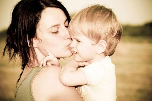 Una giovane mamma bacia il suo bimbo.