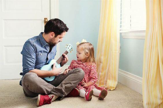 Rapporto padre-figlia: il padre suona la chitarra e la bimba canta.