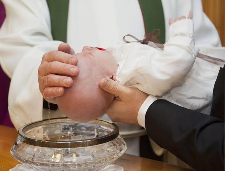 I padrini partecipano al rito del battesimo.