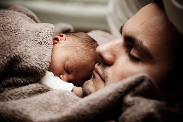 Un papà dorme con un neonato: diventare padre cambia la vita.