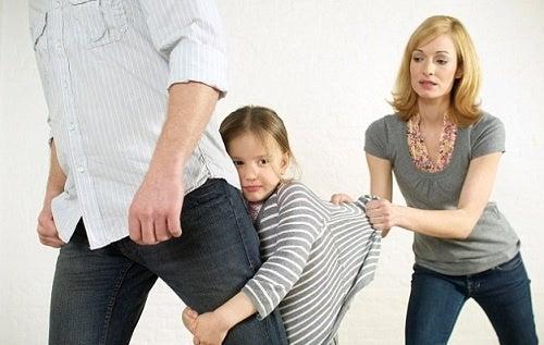 Una bambina fa i capricci attaccandosi alla gamba del padre.