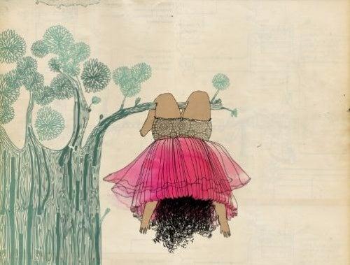 Bambina appesa a un albero a testa ingiù
