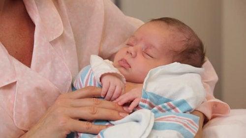Prendere in braccio il neonato dopo il parto.