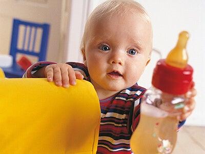 Un bambino tiene in mano il suo biberon
