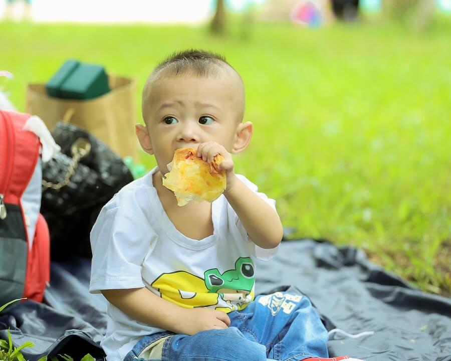 Bambino mangia una pizza: non è sempre consigliata come alimentazione dei bambini fino a 3 anni.