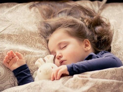 Bambina che dorme con un peluche