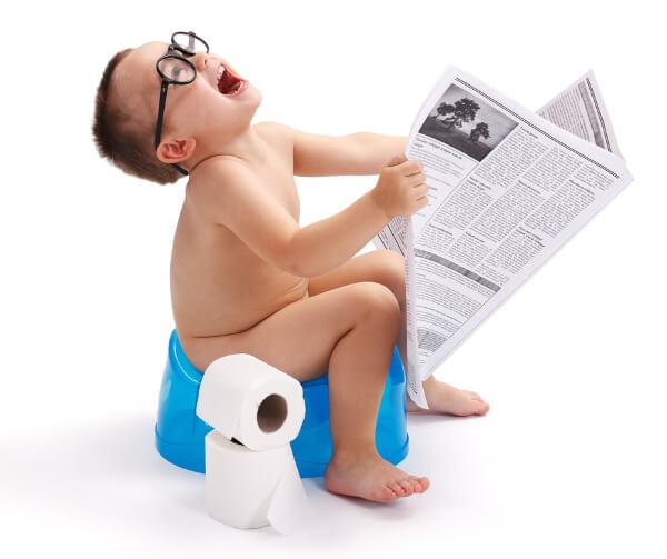 Bimbo sul vasino legge il giornale.