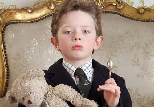 Un bambino narcisista, seduto su una poltrona principesca.