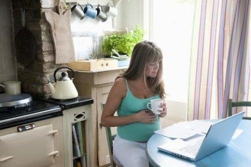 Donna incinta beve caffè in gravidanza.