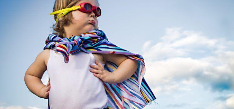 Bambino con accappatoio e occhialini in spiaggia.
