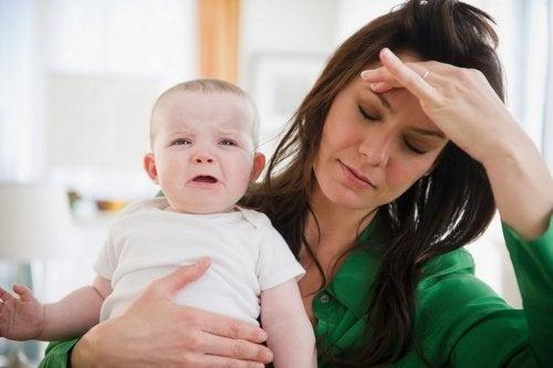 Mamma con il mal di testa e figlio che piange.