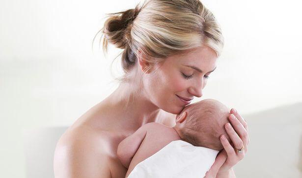 mamma abbraccia e annusa neonato