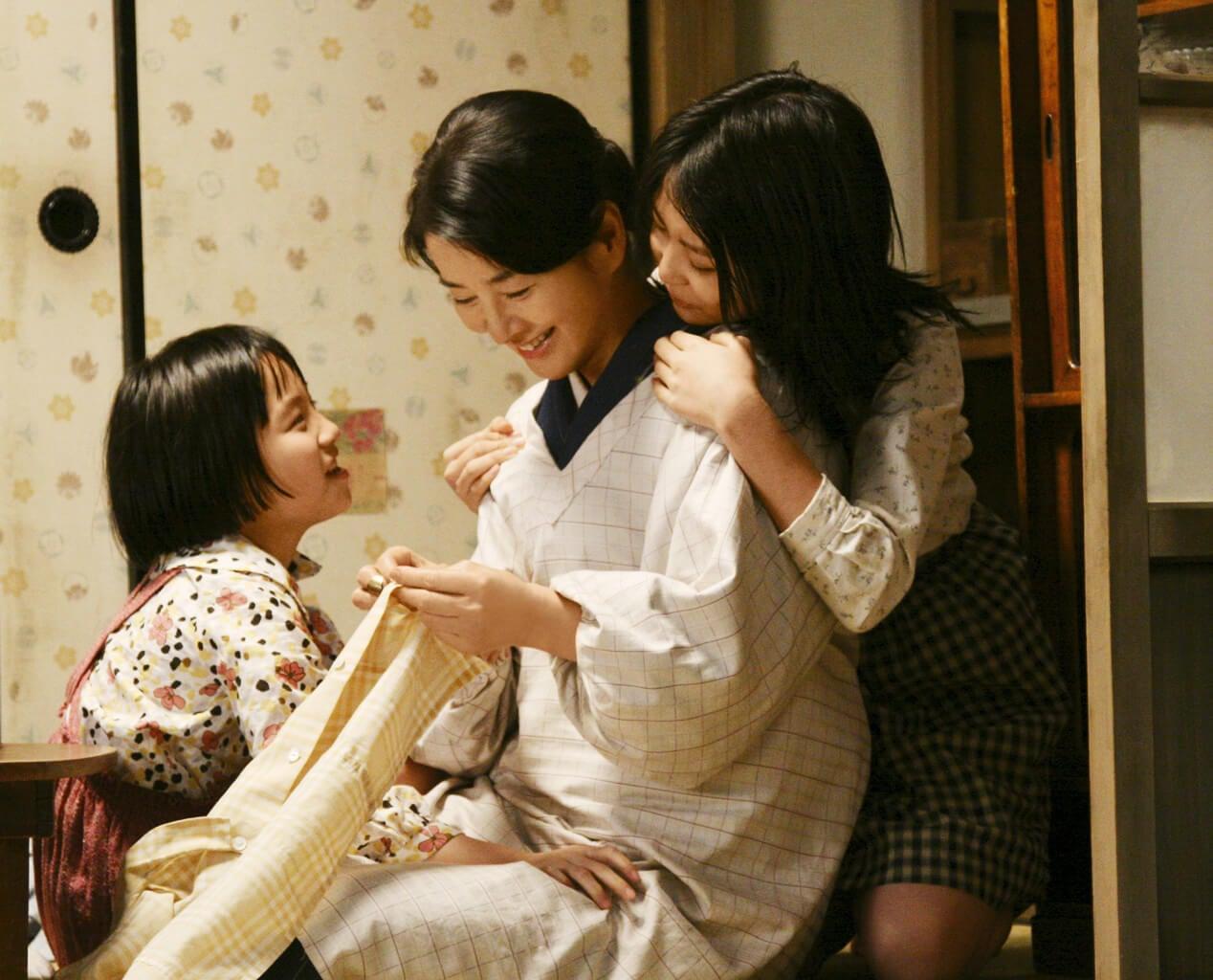 Una mamma asiatica che cuce insieme alle due figlie.