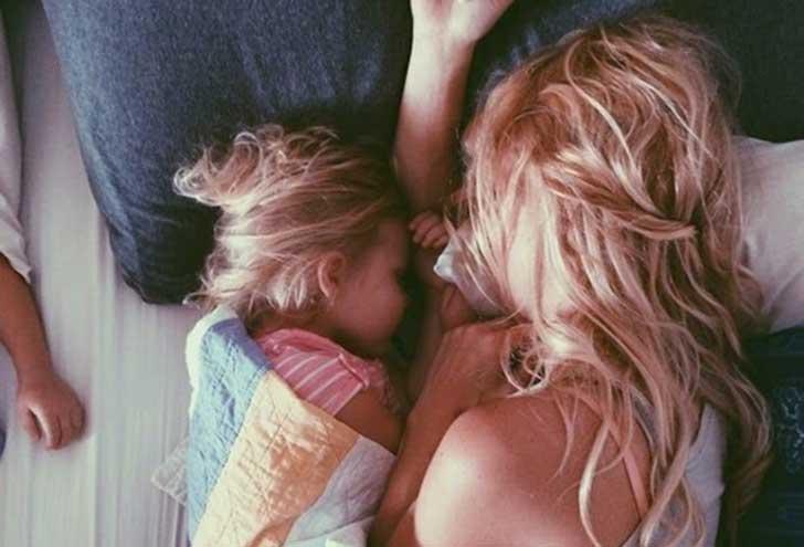 Mamma dorme con la figlia sul letto.