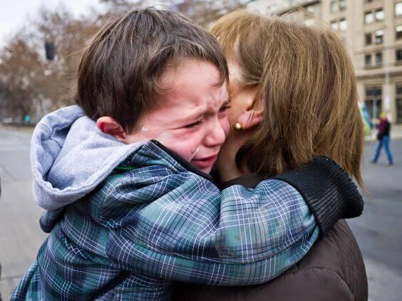 Non partire senza salutare il bambino: un bimbo piange abbracciato alla mamma.