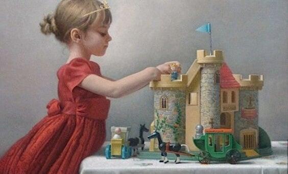 Una bambina gioca con un castello.
