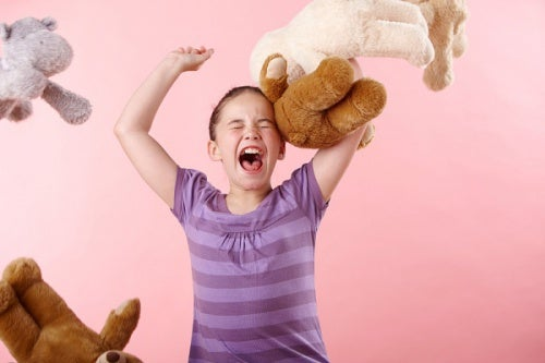 Una bambina capricciosa che tira peluches