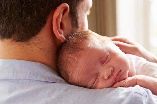 Neonato sereno tra le braccia di papà