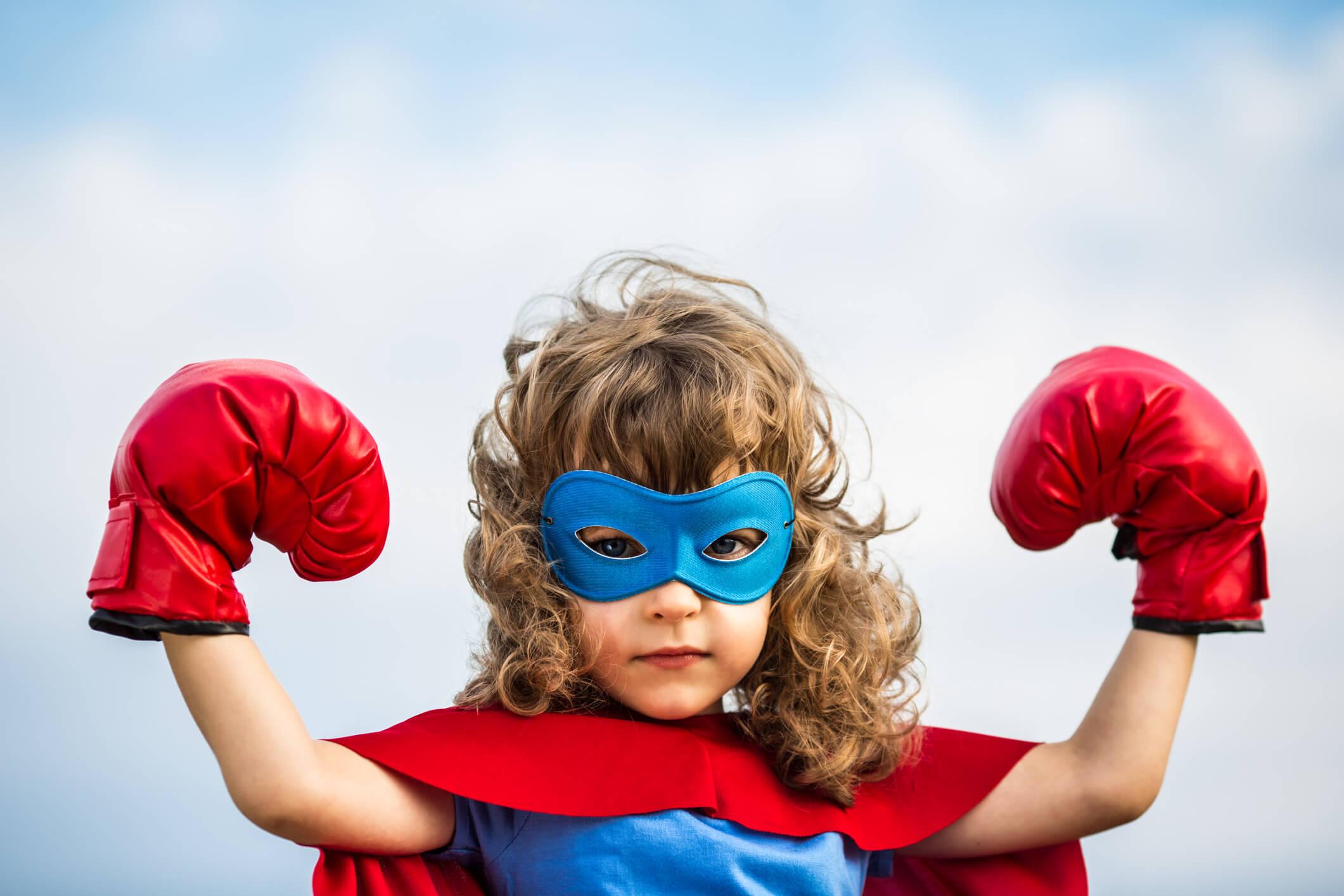 Bambina mascherata da Superman, con maschera e guantoni.