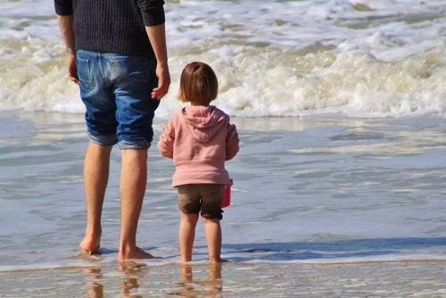 Segnali d'affetto: bimba al mare con il padre.