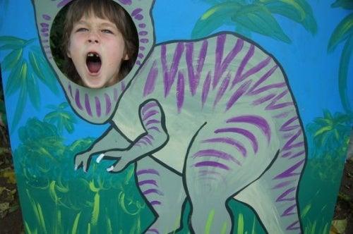 Bambino dietro figura di dinosauro