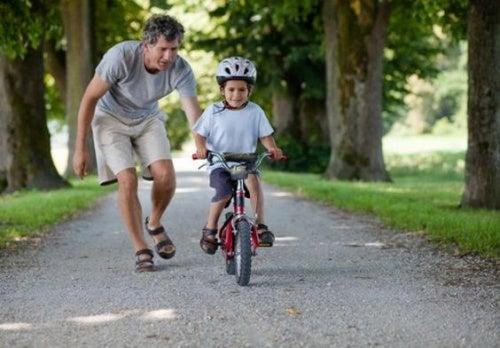 Crescere bambini felici: un padre insegna al figlio ad andare in bicicletta.