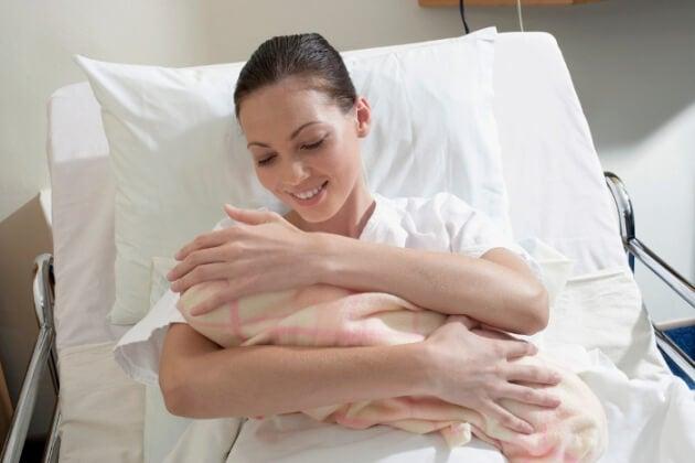 Una mamma stringe il neonato dopo il parto.