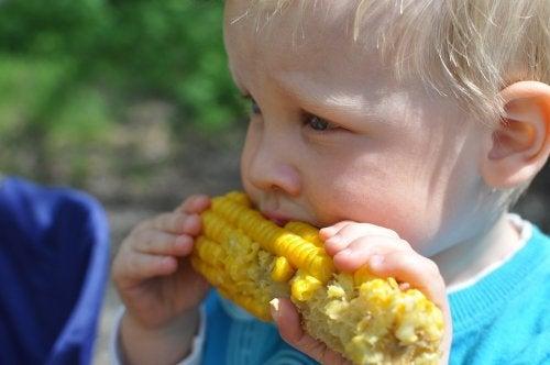 Bimbo con una pannocchia di mais:imparare a mangiare di tutto.