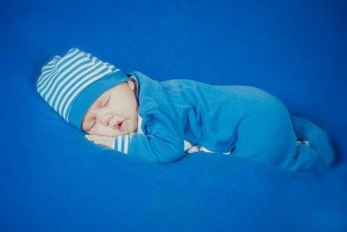 Neonato che dorme con la tutina