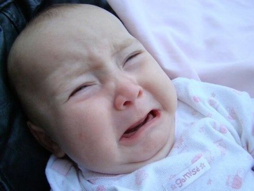 Neonato che piange per il dolore di un'infezione all'orecchio