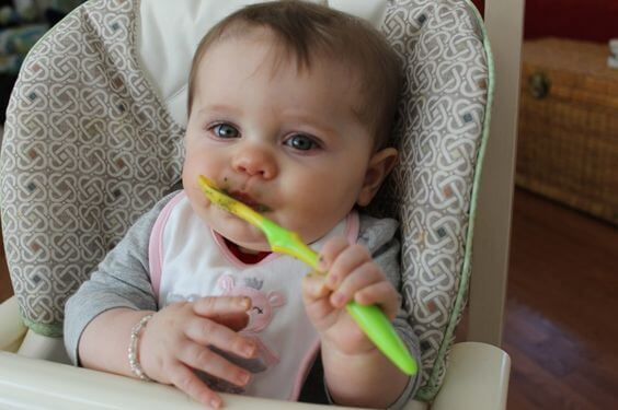 neonato mangia da solo con cucchiaio