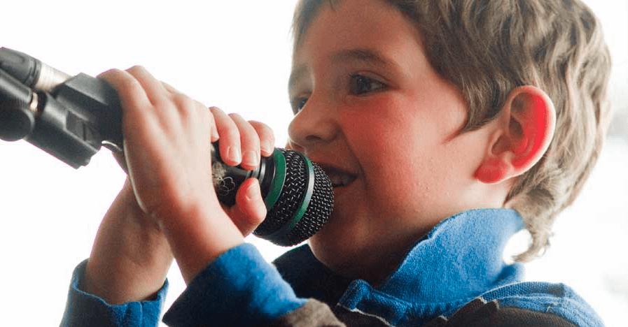 Bambino canta con un microfono