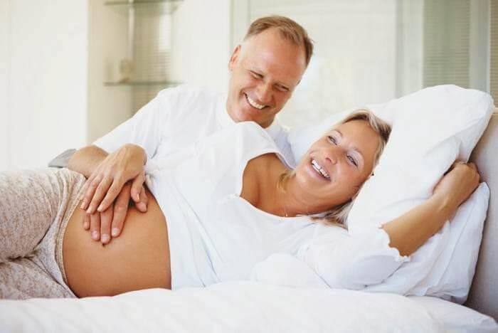 Donna incinta sorride insieme al marito