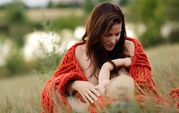Una mamma allatta in mezzo alla natura.