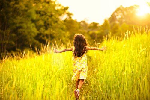 Bambina che corre in un prato con le braccia aperte