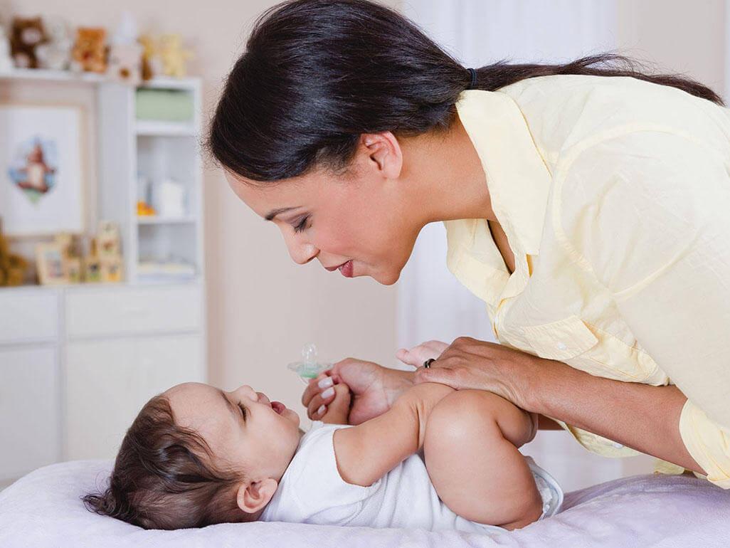 Mamma che parla al suo bambino mentre lo cambia