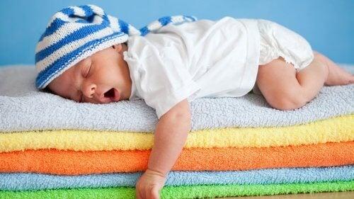 Neonato dorme su una pila di asciugamani