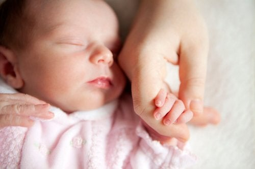 Neonata che tiene la mano della mamma mentre dorme