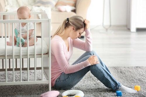 Una mamma stanca di fianco al lettino