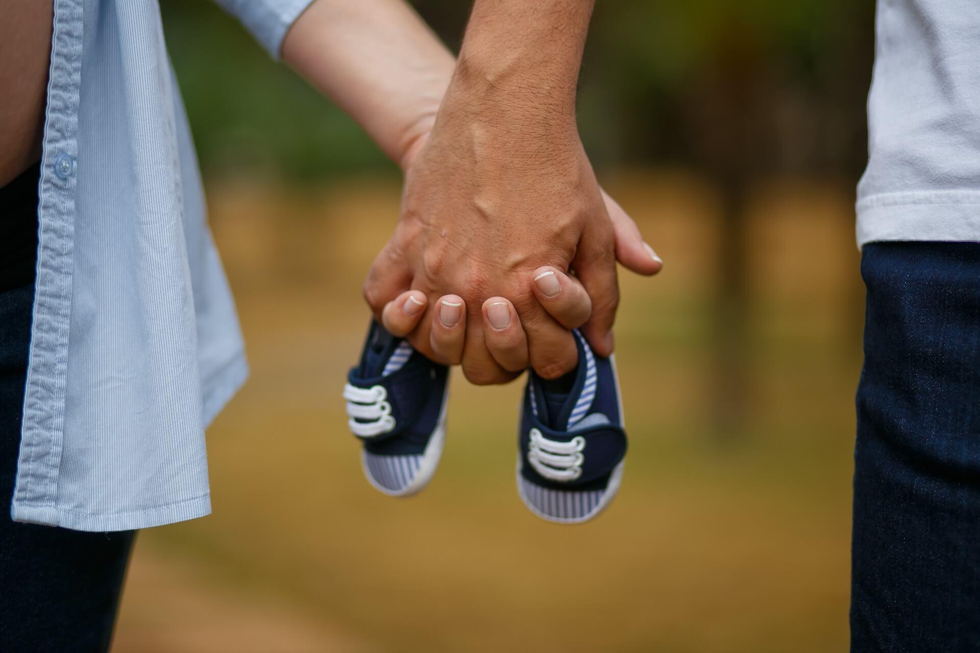 Mani unite che sorreggo delle scarpine