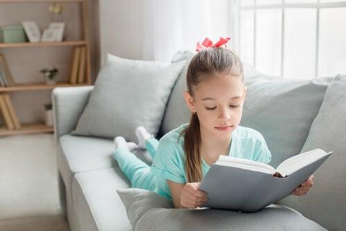 Bambina che legge un libro sul divano