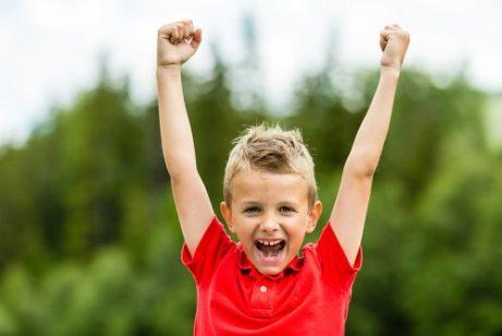 Bambino felice che esulta con le braccia alzate